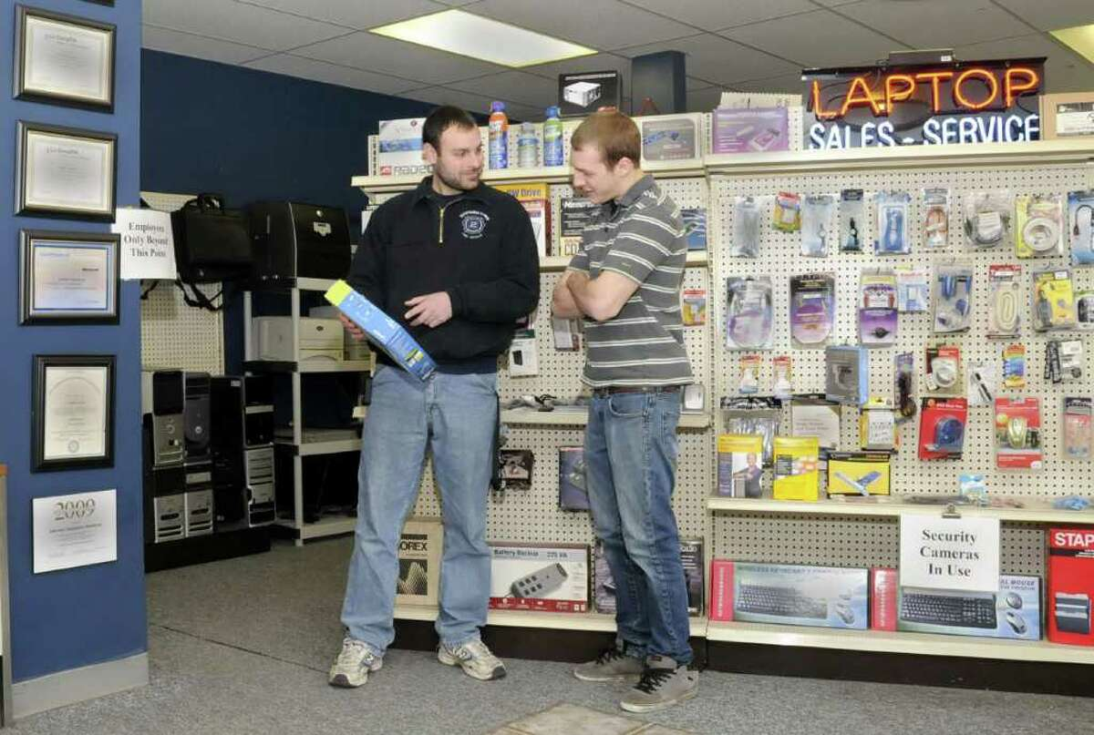 Joe Masso, left, owner of Liberty Computer Services in Newtown, discusses a product with computer technician Ben Stokes, right, of Newtown, on Thursday, Jan. 6, 2011.