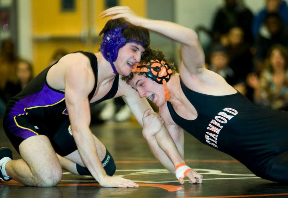 Westhill High School's Ben Villers, left, wrestles against Stamford High School's Stewart Thomas, right, during a match at Stamford High School. Photo: Kerry Sherck / Stamford Advocate Freelance