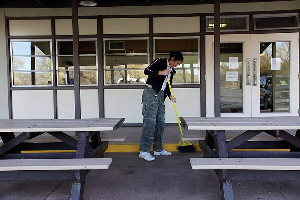 Custodian Maria Martin cleans up the area around the Rio Grande Village store in Big Bend National Park on Jan. 6, 2011.