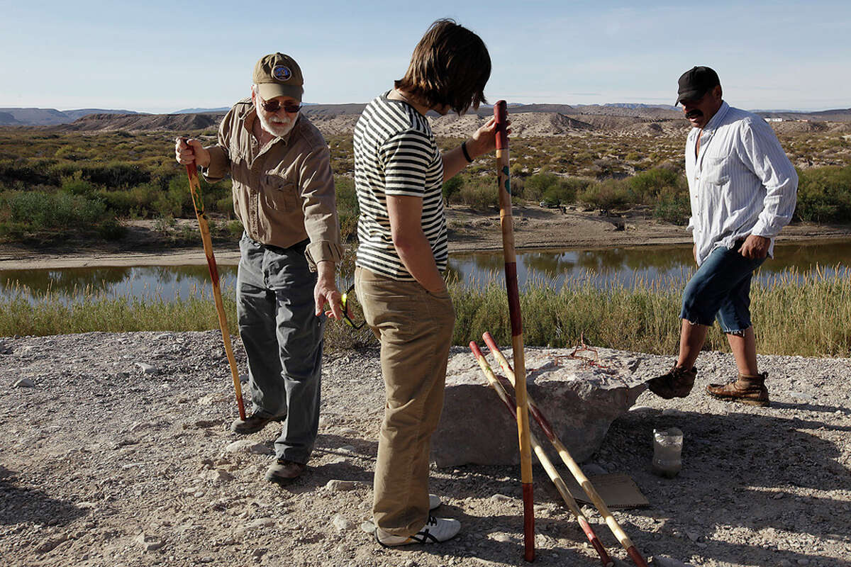 Landy Johnston and his stepson Ethan Jones of Huntsville purchase a walking stick from Sylvestre Sanchez (right), a Boquillas Del Carmen, Mexico, resident, who sells his crafts along an overlook in Big Bend National Park on Jan. 6. It was the first sale for Sanchez in three months. He said that he makes around $50 a month in sales.