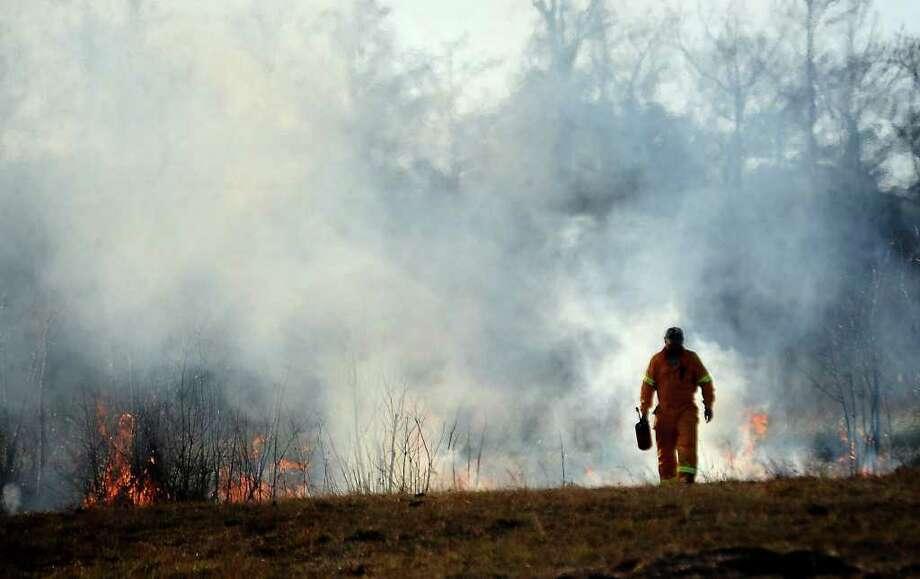 A firefighter works a marsh fire near East Roundbunch Road in Bridge City, Thursday. Tammy McKinley/The Enterprise Photo: TAMMY MCKINLEY / Beaumont