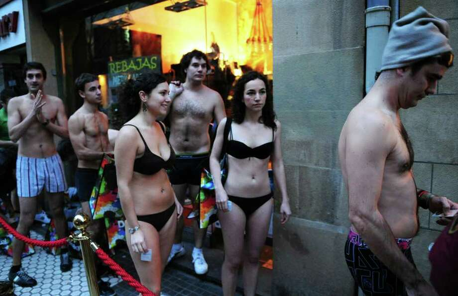 "Customers wearing underwear queue outside a ""Desigual shop on the first day of sales, on January 7, 2011 in the northern Spanish Basque city of San Sebastian. ""Desigual"" clothing company in San Sebastian, Barcelona and Marbella, asked customers to visit their stores wearing underwear in order to get free clothes during the first sale day in Spain.   AFP PHOTO/ RAFA RIVAS (Photo credit should read RAFA RIVAS/AFP/Getty Images) Photo: RAFA RIVAS"