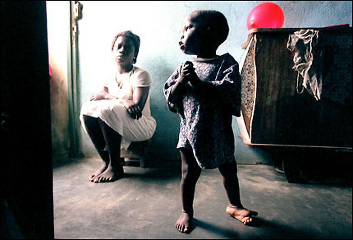 Sylvie Ahoud, 20, keeps watch over her son Parfait, 6, at their home in the slums of Abidjan, Ivory Coast. Because she could not afford to travel to a clinic for his full set of vaccinations, polio has left the boy's limbs twisted.