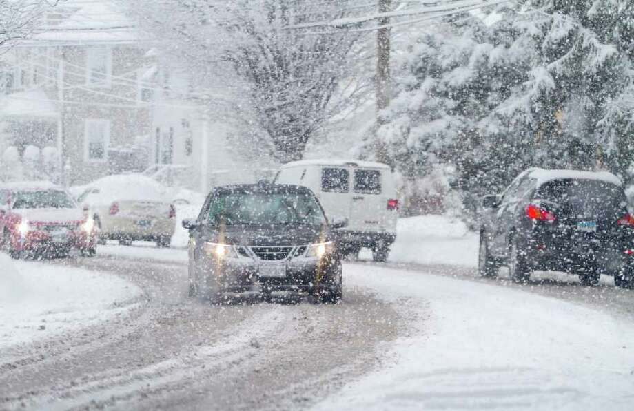 Cars make their way down hopestreet Ñ very slowly Ñ during a snow storm in Stamford, Conn. on Friday, Jan. 11, 2011. Photo: Contributed Photo / Stamford Advocate Contributed