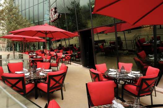 An exterior view of Beso in Las Vegas displays the restaurant's bright red dining furniture. COURTESY