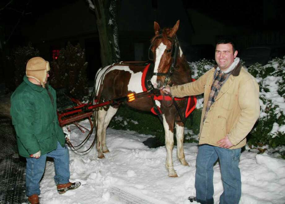 John Anello holds the reins of Big Boy, a horse that had gotten loose in Cos Cob as he was pulling a sleigh Friday night, as the horse's owner and John's father, Blaise Anello, is shown at left. The horse had escaped from Blaise Anello, who was riding in the sleigh. Photo by Nick Dagostino. Photo: Contributed Photo / Greenwich Time Contributed