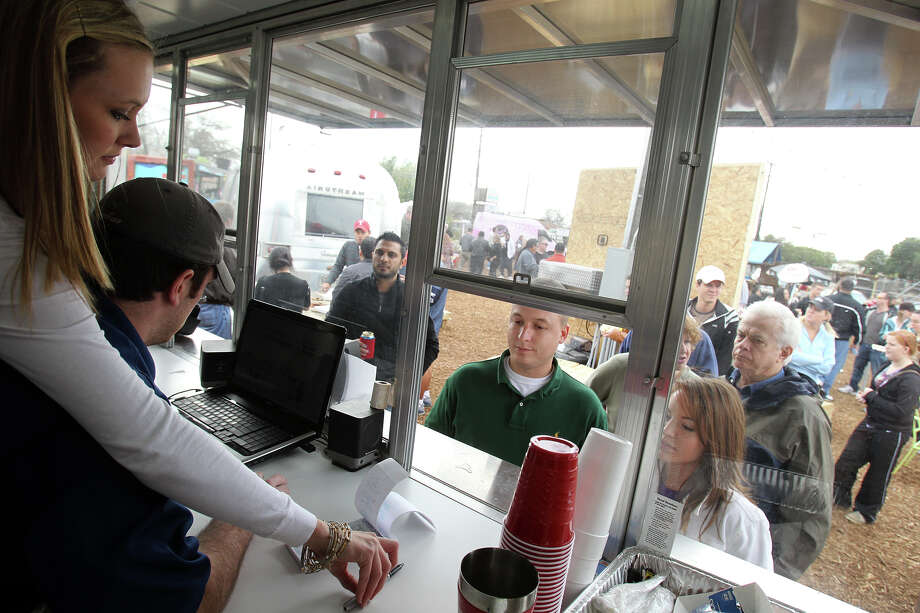 Jessie Mangum (left) and Travis Mangum take orders from customers at K Hill BBQ Company during the grand opening of the Boardwalk on Bulverde. The wait at many of the food stations Saturday was a half-hour or more. Photo: Jennifer Whitney/Special To The Express-News