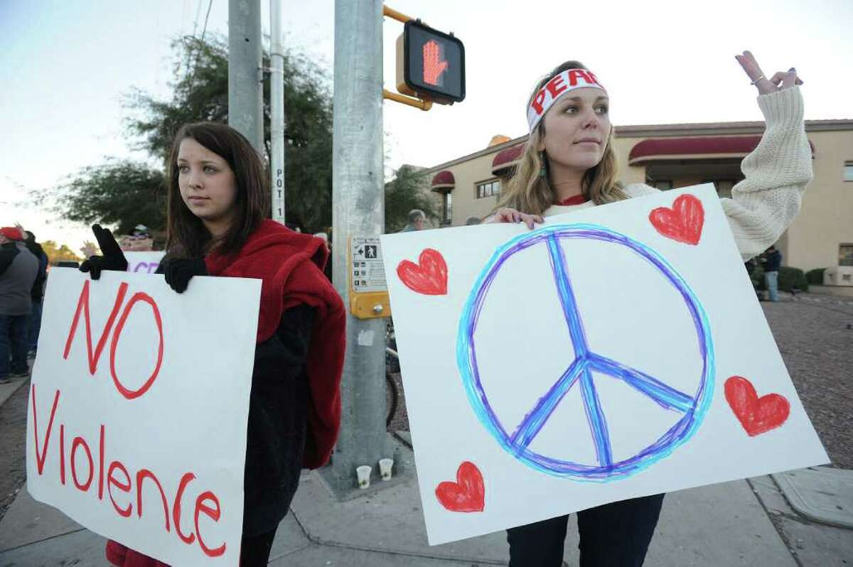 TUCSON, AZ - JANUARY 8: Lily Wool (L), 19, of Tucson, Arizona and Vera Rapcsak, 20, of Tucson, Arizona hold signs outside the Tucson office of U.S. Rep. Gabrielle Giffords (D-AZ), who was shot during an event in front of a Safeway grocery store January 8, 2011 in Tuscon, Arizona. U.S. Rep. Gabrielle Giffords (D-AZ) was shot in the head at a public event entitled