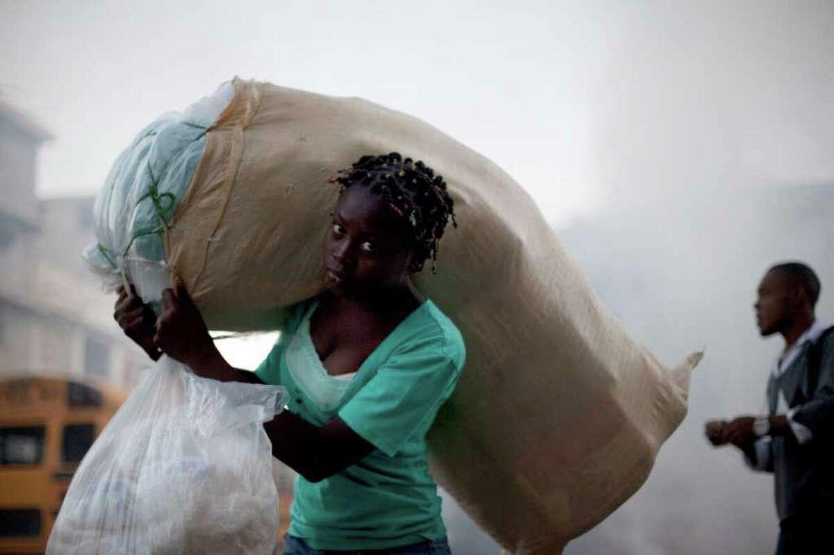 PORT-AU-PRINCE, HAITI - JAN 2011: A woman carries a sack on her back through downtown Port-au-Prince, Haiti, Wednesday Jan 5, 2011. (AP Photo/Ramon Espinosa)