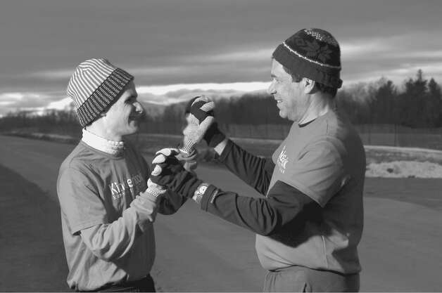 Ralph Sansaricq, right, and his son Robert share a playful high five after running together in Kinderhook one day in December. After he runs, Robert,  who is autistic, smiles more easily and holds his head higher with pride. (Philip Kamrass / Times Union ) Photo: Philip Kamrass