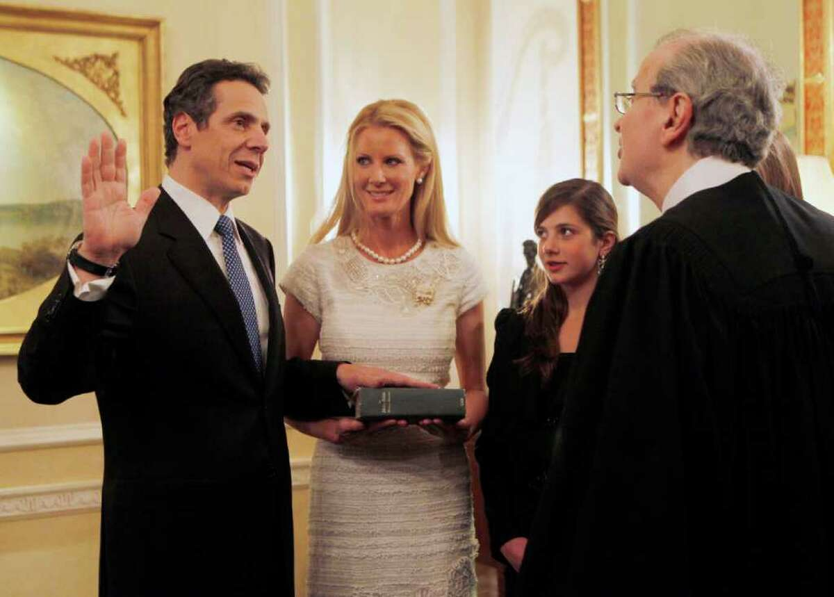 New York Gov. Andrew Cuomo, left, is sworn in by Chief Judge Jonathan Lippman during a private ceremony at the Executive Mansion in Albany, N.Y. on Friday, Dec. 31, 2010. Cuomo's girlfriend Sandra Lee holds the Bible as his daughter Michaela Cuomo looks on. (AP Photo/Mike Groll)
