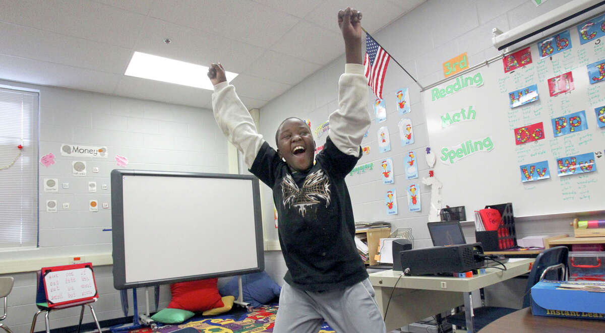 Nduwimana Richard, 9, celebrates in class at Braun Station Elementary School after completing a math exercise. Richard, a refugee, is hearing impaired and has learned to sign with the help of teachers.