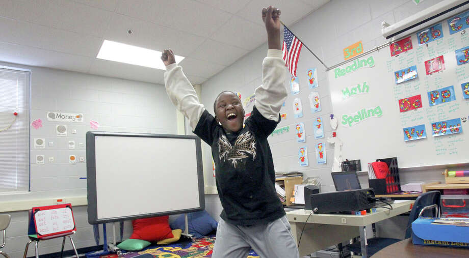 Nduwimana Richard, 9, celebrates in class at Braun Station Elementary School after completing a math exercise. Richard, a refugee, is hearing impaired and has learned to sign with the help of teachers. Photo: JOHN DAVENPORT/jdavenport@express-news.net