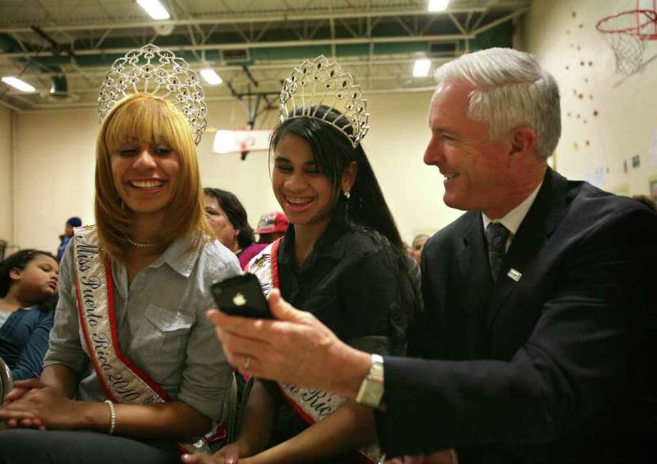 Bridgeport Mayor Bill Finch, right, shows his Tweet of a photo that he snapped of Miss Puerto Rico Fairfield County 2010 Jessica Santos, left, and Miss Teen Puerto Rico Fairfield County 2010 Janice Cancel during a visit to the Three King's Day celebration at Marin School in Bridgeport on Thursday, January 6, 2011. Photo: Brian A. Pounds / Connecticut Post
