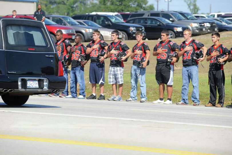 Members of the Kirbyville football team stand at attention as a funeral procession for legendary New