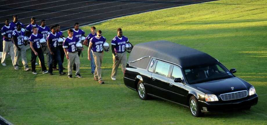 Members of the Newton football team follow the hearse carrying the body of Curtis Barbay during the public memorial service to honor is life and pay final respects at Newton High School in Newton, Tuesday. Tammy McKinley/The Enterprise Photo: TAMMY MCKINLEY, MBR / Beaumont