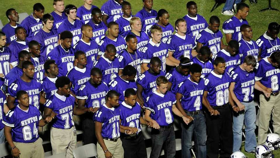 The 2010 Newton football team link pinkies during the school song as hundreds of friends, family and
