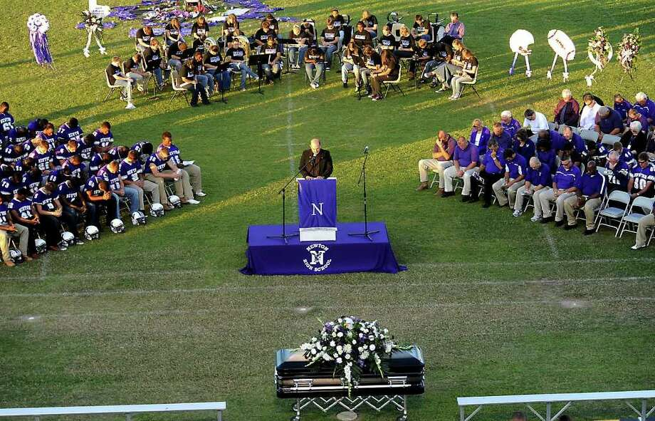 Father Ron Foshage offers the Invocation as hundreds of friends, family and fans gather together to honor the life and pay final respects to Coach Curtis Barbay during a public memorial service in his honor at Newton High School in Newton, Tuesday. Tammy McKinley/The Enterprise Photo: TAMMY MCKINLEY, MBR / Beaumont