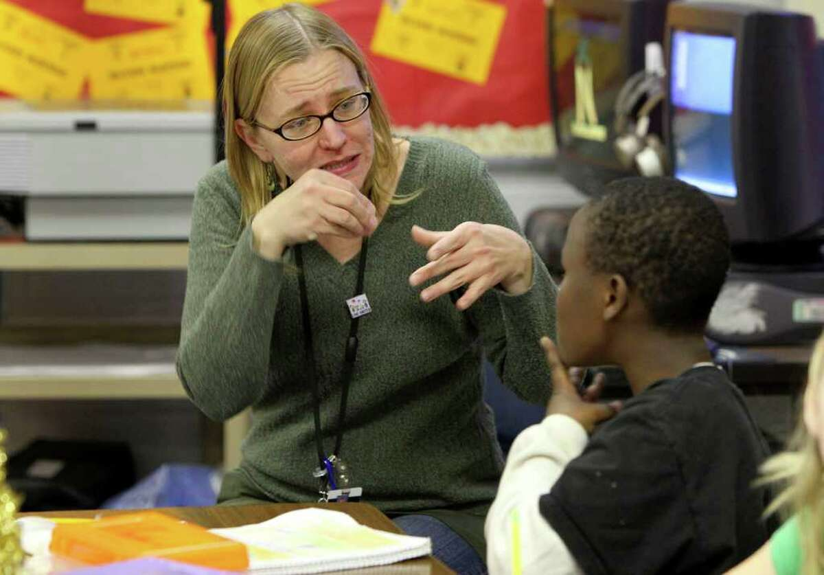 Teacher Rose Greive (left) signs with hearing impaired student Nduwimana Richard ,9, (right) during class at Braun Station Elementary School Tuesday December 14, 2010. Richard and his family moved here from Tanzania and he didn't learn sign language until he was seven. JOHN DAVENPORT/jdavenport@express-news