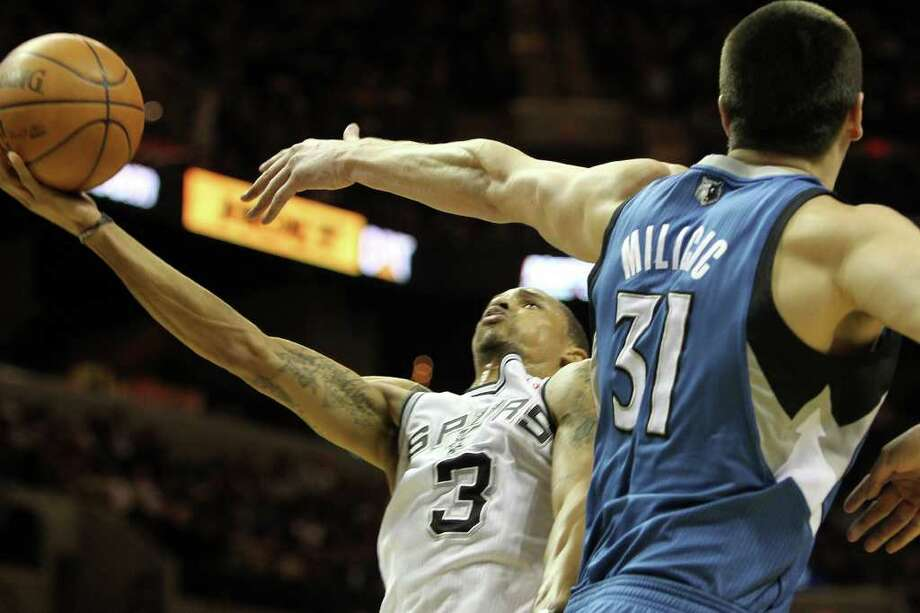 George Hill shoots in the first half guarded by the Timberwolves' Darko Milicic in the first half of the Spurs vs. Minnesota Timberwolves matchup at the AT&T Center, Sunday, January 9, 2011. Photo: JENNIFER WHITNEY, Special To The Express-News / special to the Express-News