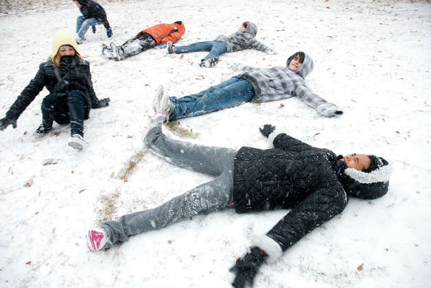 A group of kids, bundled up for the cold weather, makes snow angels near the Texas-Arkansas border in Texarkana, Texas.