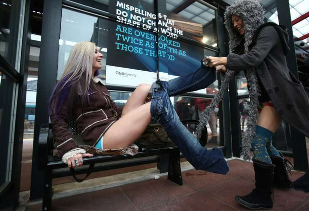 """Jane Merkutova has her pants removed by her friend Ciara Sampaio during Seattle's second """"No-Pants Light Rail Ride"""" on Sunday, Jan. 9, 2011. During the event hundreds of train passengers took off their pants, surprising other riders and bystanders. The event took place in other cities around the globe on Sunday."""
