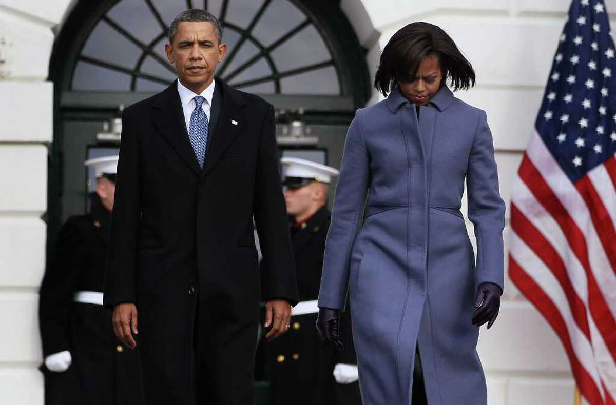 WASHINGTON, DC - JANUARY 10: U.S. President Barack Obama and first lady Michele Obama walk up to participate in a moment of silence to honor those killed and wounded during a shooting in Tucson, Arizona on January 10, 2011 in Washington, DC. President Barack Obama called on the nation to observe a moment of silence today at 11:00am in honor of the six people killed and at least 13 others wounded including U.S. Rep. Gabrielle Giffords (D-AZ) when a gunman opened fire at a public event held at Tucson Safeway supermarket. (Photo by Mark Wilson/Getty Images) *** Local Caption *** Michele Obama;Barack Obama