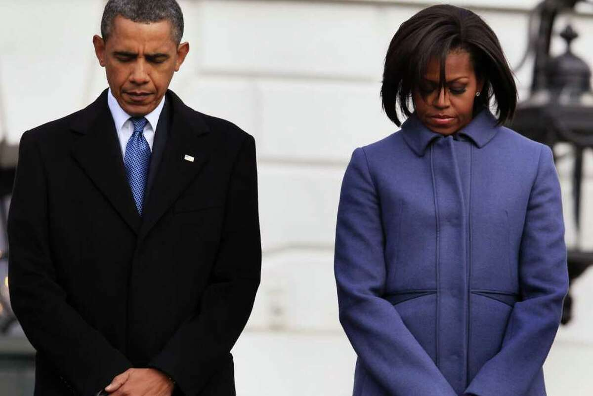 WASHINGTON, DC - JANUARY 10: U.S. President Barack Obama (L) and first lady Michele Obama participate in a moment of silence to honor those killed and wounded during a shooting in Tucson, Arizona on January 10, 2011 in Washington, DC. President Obama called on the nation to observe a moment of silence today at 11:00 a.m. in honor of the six people killed and at least 13 others wounded, including U.S. Rep. Gabrielle Giffords (D-AZ), when a gunman opened fire at a public event held at Tucson Safeway supermarket. (Photo by Mark Wilson/Getty Images) *** Local Caption *** Michele Obama;Barack Obama