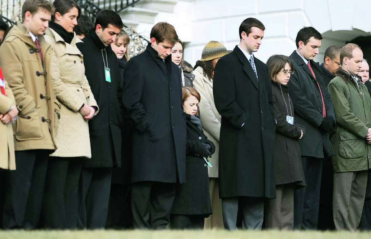WASHINGTON, DC - JANUARY 10: White House staff observe a moment of silence to honor those killed and wounded during a shooting in Tucson, Arizona ouside the White House on January 10, 2011 in Washington, DC. President Barack Obama called on the nation to observe a moment of silence today at 11:00am in honor of the six people killed and at least 13 others wounded including U.S. Rep. Gabrielle Giffords (D-AZ) when a gunman opened fire at a public event held at Tucson Safeway supermarket. (Photo by Mark Wilson/Getty Images) *** Local Caption *** Michele Obama;Barack Obama