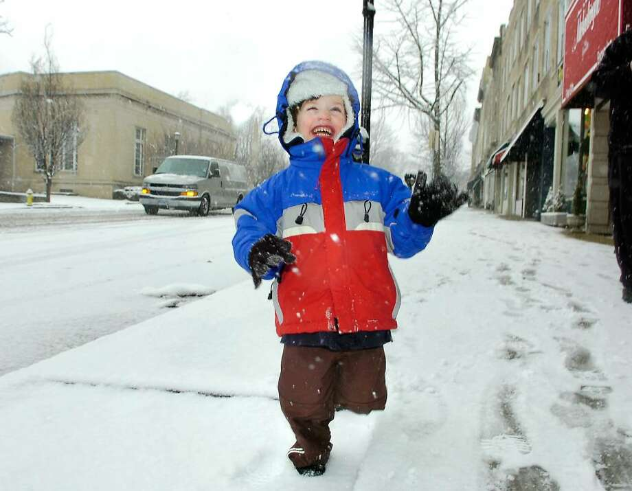 Nicholas Aravides, 3, of Greenwich, jumps for joy while running in the snow on Greenwich Ave. Wednesday morning, Feb. 10th, 2010, with his father, George Aravides (not in photo) and his sister Alexandra Aravides (also not in photo).  The younger Aravides was happy as his daycare school  was cancelled and he  got to spend the day in the snow with his dada and sister. Photo: Bob Luckey / Greenwich Time
