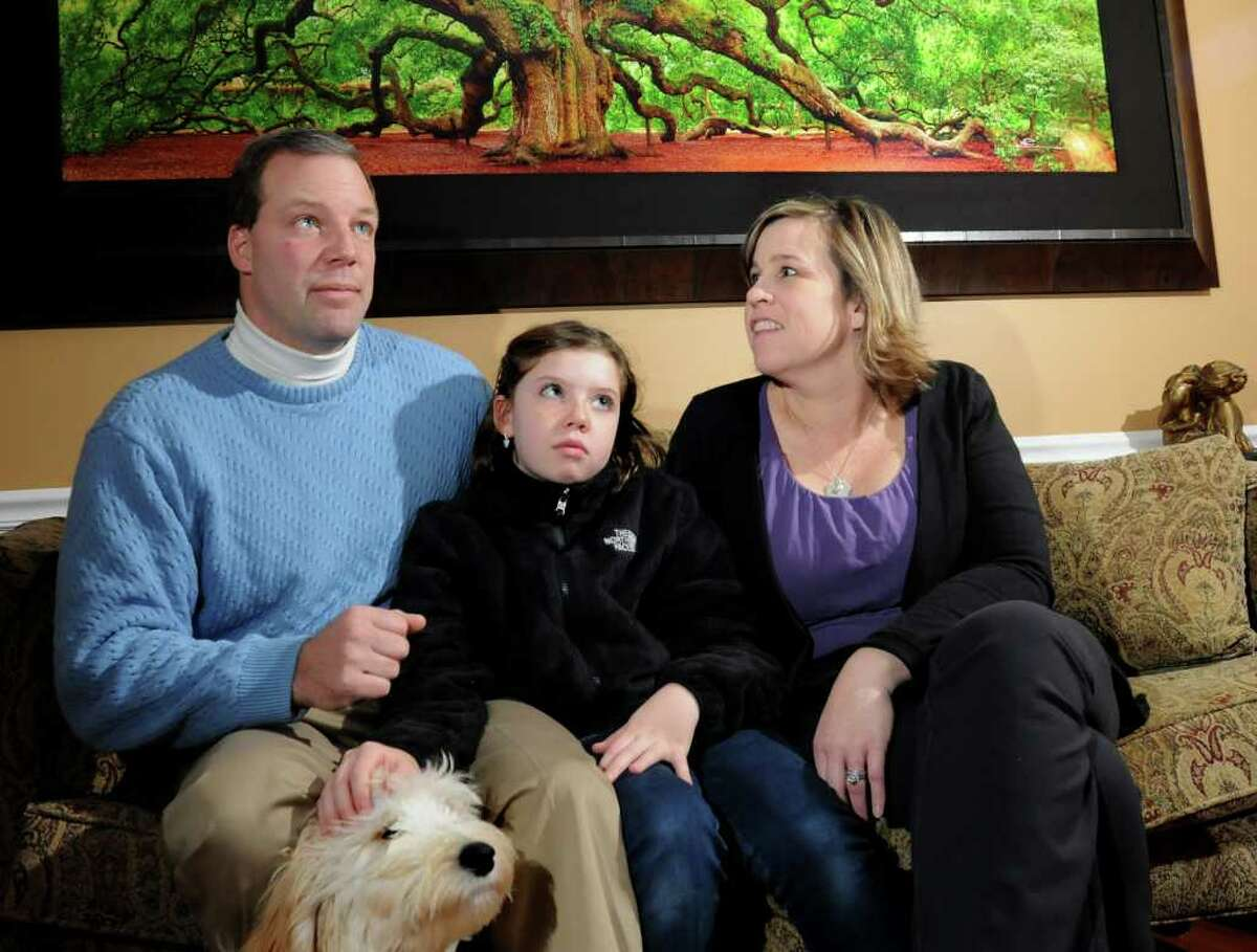 Todd and Beth Silaika sit with their daughter Victoria, 11, one of their six children on Friday, Jan. 8, 2011, in Clifton Park, N.Y. The Silaika's talk about their home solar project. (Cindy Schultz / Times Union)