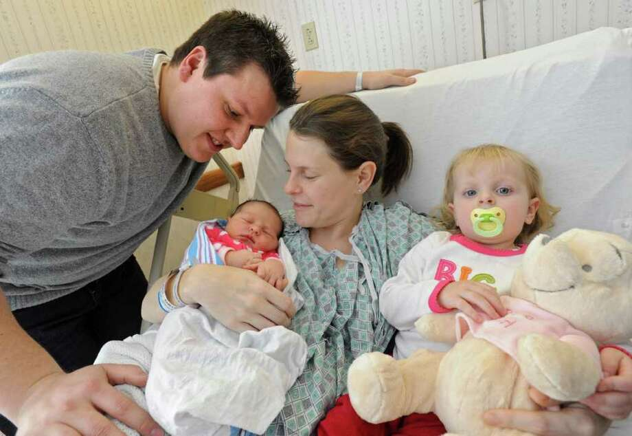From left, the Dumas family, Tyler, Christina, and Madison, age 2, spend time with the new addition to the family, Alexis Grace, at Bellevue Woman's Center in Schenectady, NY on January 10, 2011. The couple unexpectedly delivered their child at their Stillwater home Sunday afternoon with the help of a 911 dispatcher. (Lori Van Buren / Times Union) Photo: Lori Van Buren