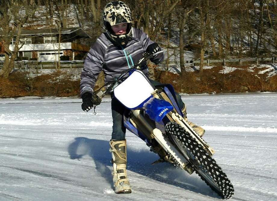 Billy Landon, 16, of Shelton, slides his motorcycle across the ice at Pink House Cove in Derby, Sunday, Jan. 10, 2011. Photo: Phil Noel / Connecticut Post