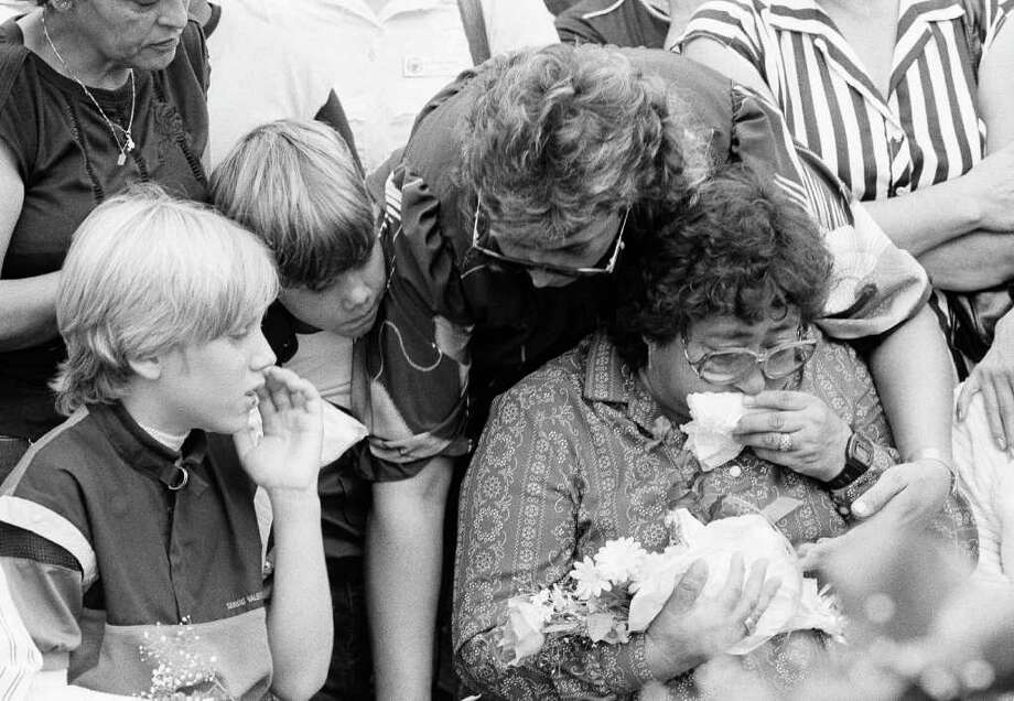 Adelina Hernandez, right, the mother of slain McDonald's massacre victim Omar Hernandez, is consoled by Esperanza Coleman at graveside services, July 23, 1984 in Chula Vista, California. Mrs. Coleman's nephew, Joshua, far left, was wounded in the attack that killed Omar Hernandez. (AP Photo/Jimmy Dorantes) Photo: Jimmy Dorantes, STR / AP1984