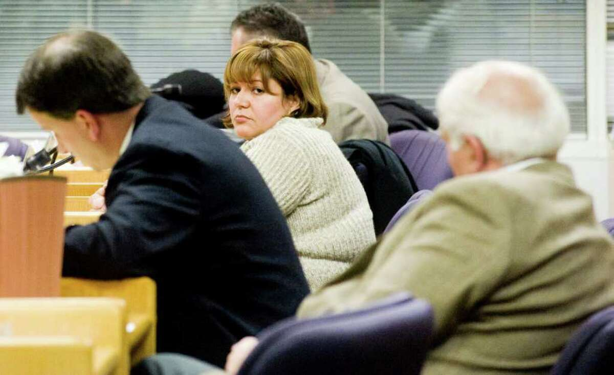 City human resources generalist Tania Barnes, center, fields questions from Tarzia's attorney Joe Sargent, left, as the Board of Ethics holds its second hearing in the complaint Barnes filed against Republican Board of Finance Chairman Joe Tarzia, right, at the Government Center in Stamford, Conn., Monday, January 10, 2011.