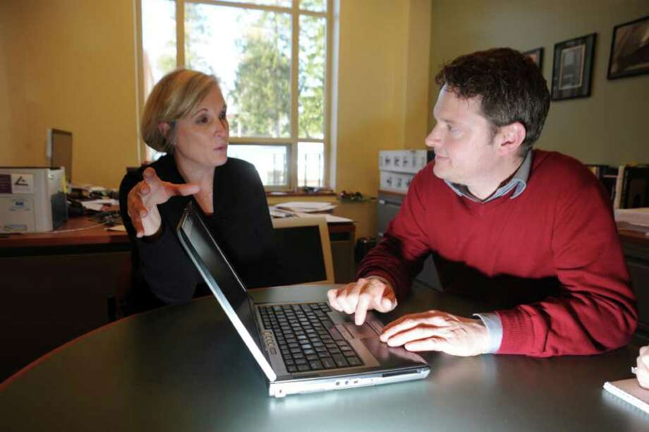 Convent of the Sacred Hearts fourth-grade teacher, Kerri Moore, left, speaks with Karl Haeseler, the school's director of educational technology, about the variety of computer programs that allow them to give online lessons on Tuesday, Jan. 11, 2011. Photo: Helen Neafsey / Greenwich Time