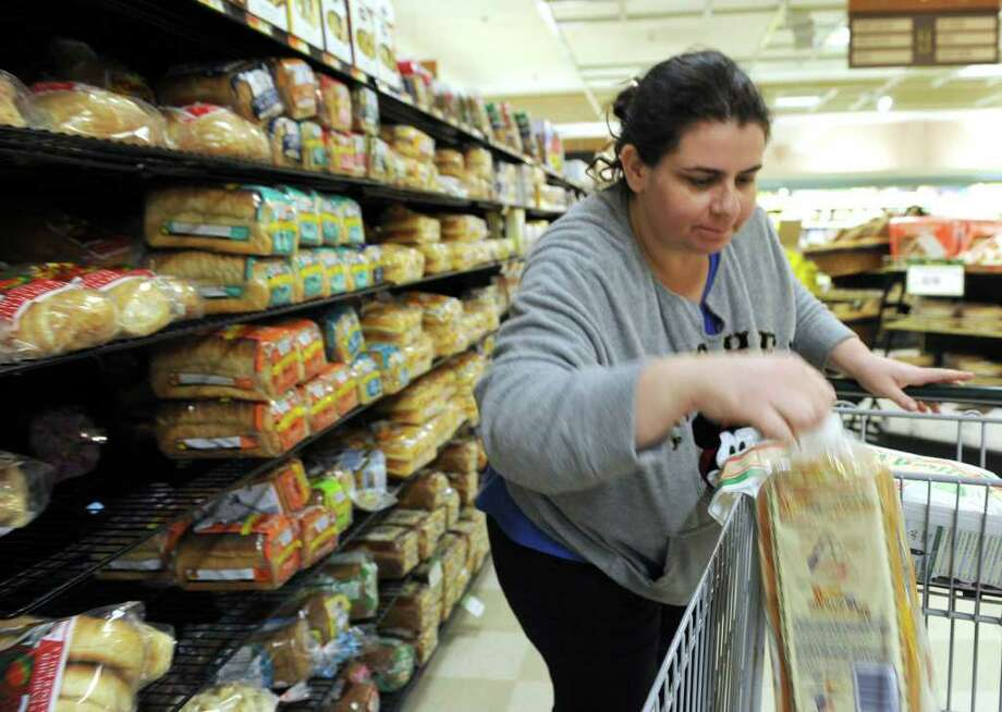 Alessandra Zocolotti of Danbury stocks up on bread, milk and other essentials Tueday afternoon at Caraluzzi's Bethel Food market in preparation for Wednesday's snow storm. Photo taken Tuesday, January 11, 2011. Photo: Carol Kaliff / The News-Times