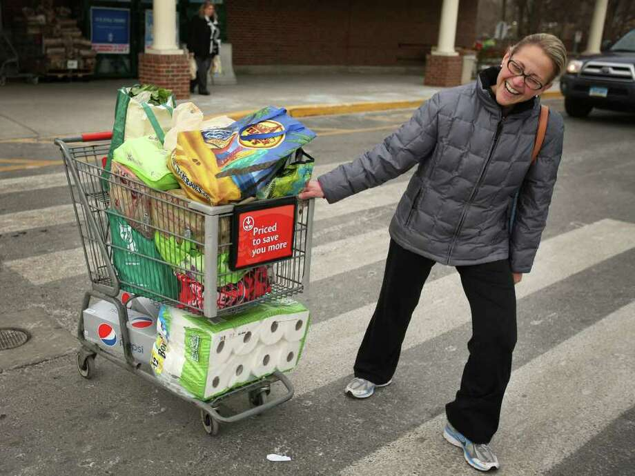Jessica Ryan of Easton pulls her heavy shopping cart full of groceries at Stop & Shop on King's Highway in Fairfield on Tuesday, January 11, 2011. Ryan said she went shopping a day early this week because of the coming snowstorm. Photo: Brian A. Pounds / Connecticut Post