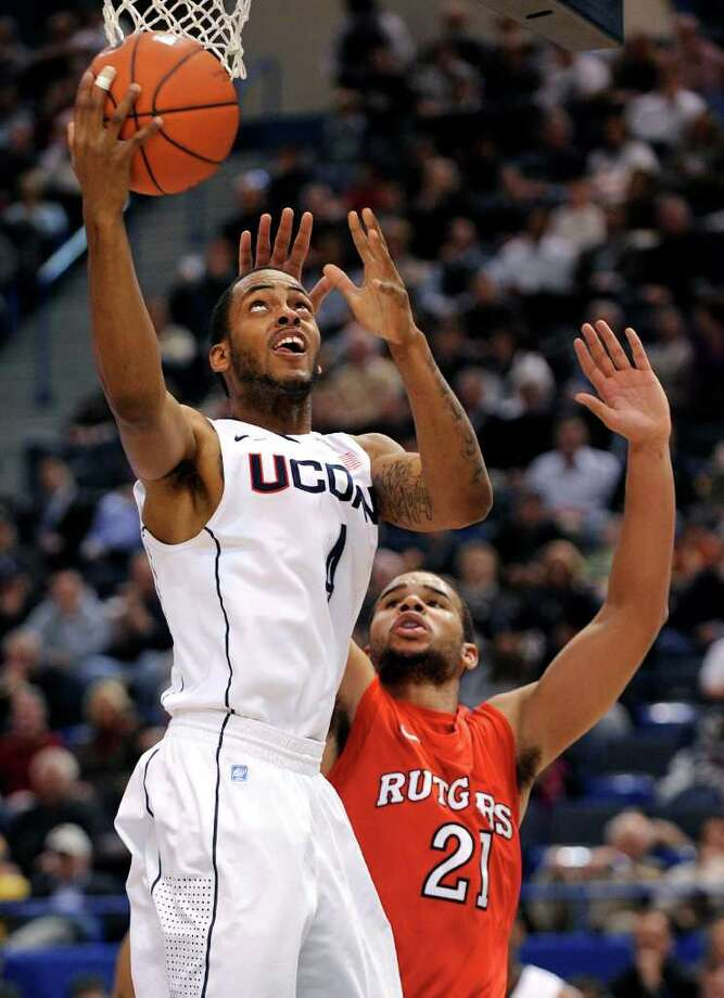 Connecticut's Jamal Coombs-McDaniel, left, drives past Rutgers' Austin Johnson during the first half of an NCAA college basketball game in Hartford, Conn., on Tuesday, Jan. 11, 2011. (AP Photo/Fred Beckham) Photo: AP
