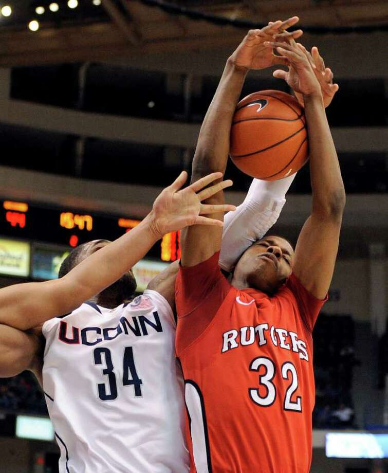 Connecticut's Alex Oriakhi, left, and Rutgers' Mike Poole reach for a rebound during the second half of Connecticut's 67-53 victory in an NCAA college basketball game in Hartford, Conn., on Tuesday, Jan. 11, 2011. Poole scored a team-high 11 points and had 10 rebounds, Oriakhi scored 17 points and had 12 rebounds. (AP Photo/Fred Beckham) Photo: AP