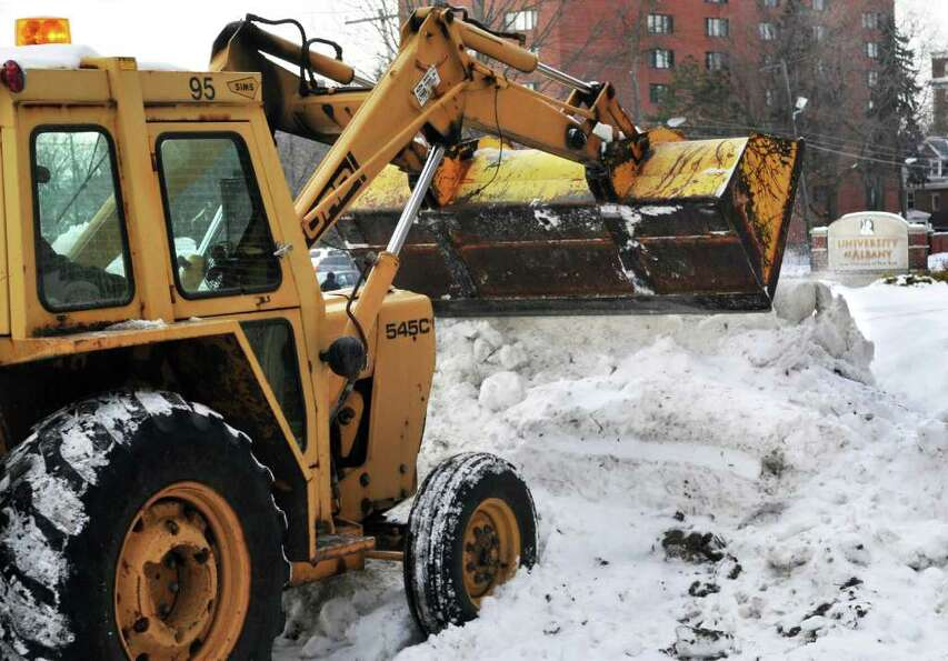 Crews work to remove snow from UAlbany's downtown campus parking lots before for the next predicted