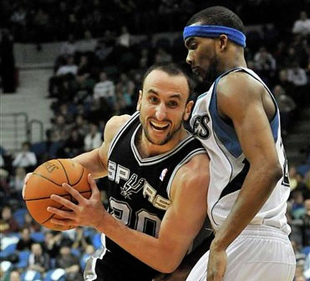 Manu Ginobili drives by Corey Brewer during the second half. (Associated Press)
