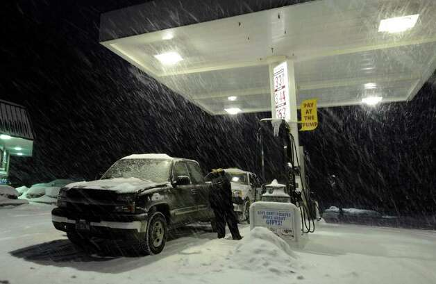 As the snow piles up, an early commuter pumps gas at the Stewarts on Route 9P in Malta on Wednesday, Jan. 12, 2011. (Skip Dickstein / Times Union) Photo: SKIP DICKSTEIN