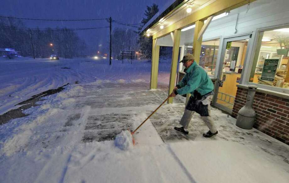 Store owner Ron DeLucia move snow from the front of his store, DeLucia's Grocery Deli, in Malta Ridge on Wednesday, Jan. 12, 2011.  DeLucia said that it was the second time he  had to remove snow from the front of the store since he arrived at 4 a.m. (Skip Dickstein / Times Union) Photo: SKIP DICKSTEIN