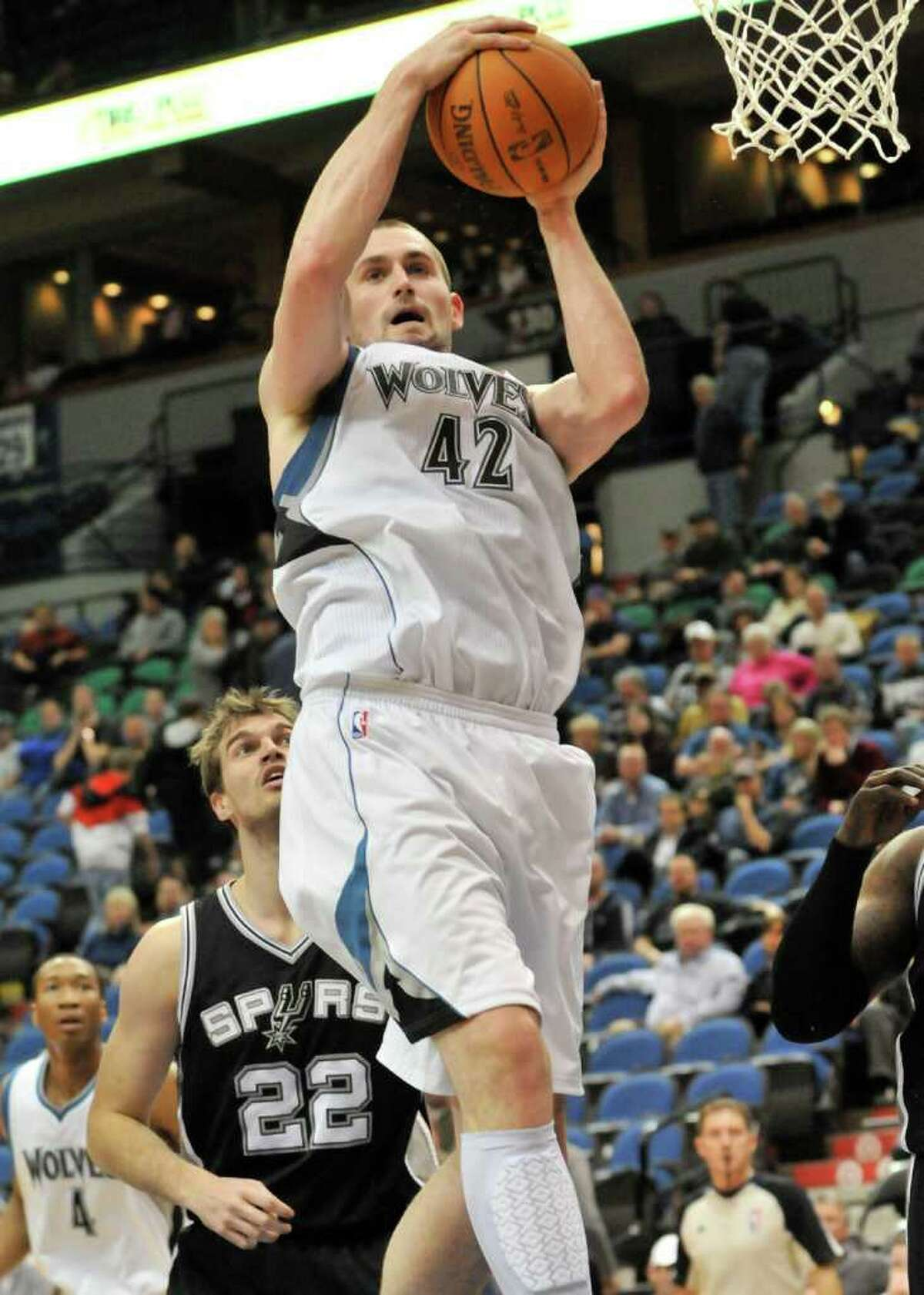Minnesota Timberwolves' Kevin Love grabs a rebound as San Antonio Spurs' Tiago Splitter looks on during the second half of an NBA basketball game Tuesday, Jan. 11, 2011 in Minneapolis. The Spurs won 107-96.