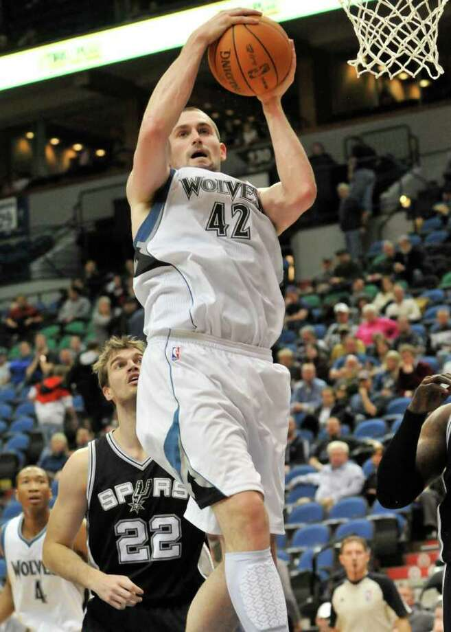 Minnesota Timberwolves' Kevin Love grabs a rebound as San Antonio Spurs' Tiago Splitter looks on during the second half of an NBA basketball game Tuesday, Jan. 11, 2011 in Minneapolis. The Spurs won 107-96. Photo: AP