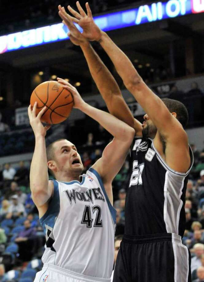 Minnesota Timberwolves' Kevin Love, left, goes to the basket as San Antonio Spurs' Tim Duncan defends during the first half of an NBA basketball game Tuesday, Jan. 11, 2011, in Minneapolis. Photo: AP