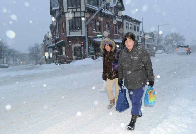From left, Marina Perez and Sylvia Gonzales, both Greenwich Hospital workers, walk east on the Post Road at the top of Greenwich Avenue on their commute into work during the snowstorm, Wednesdy morning, Jan. 12, 2011. Photo: Bob Luckey / Greenwich Time