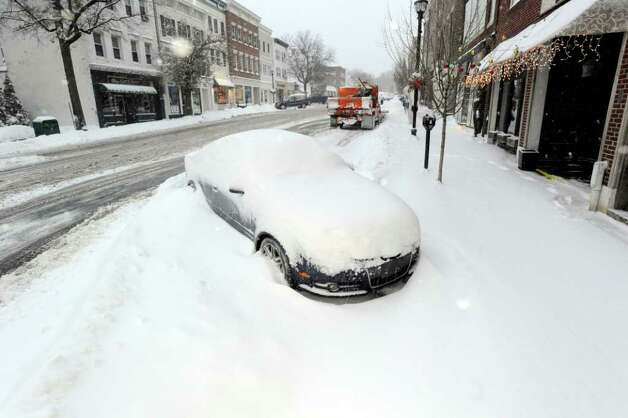 A snow-covered car parked at the bottom of Greenwich Avenue, Wednesday morning, Jan. 12, 2011. Photo: Bob Luckey / Greenwich Time