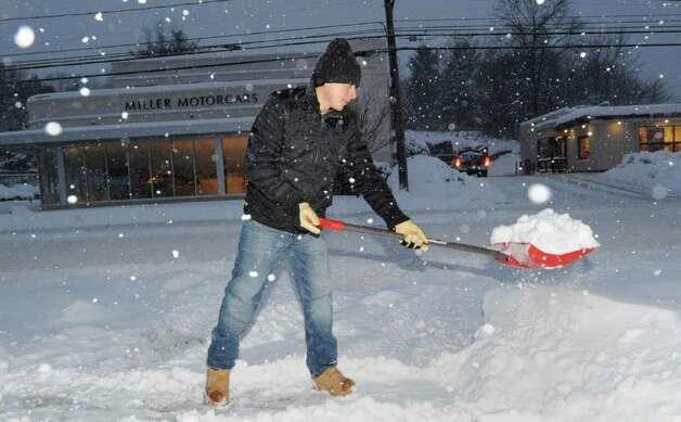 Wilbert Tarazona shovels snow from the walkway of Greenwich Hardware on West Putnam Avenue, Wednesday morning, Jan. 12, 2011. Photo: Bob Luckey / Greenwich Time